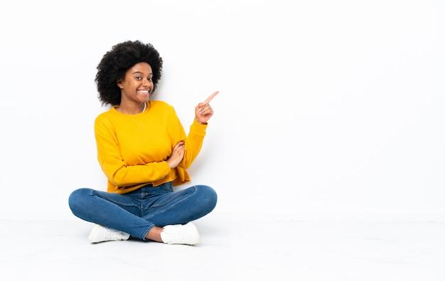 Jovem americana africano sentado no chão, apontando o dedo para o lado