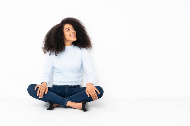 Jovem americana africano sentado no chão olhando para cima enquanto sorrindo