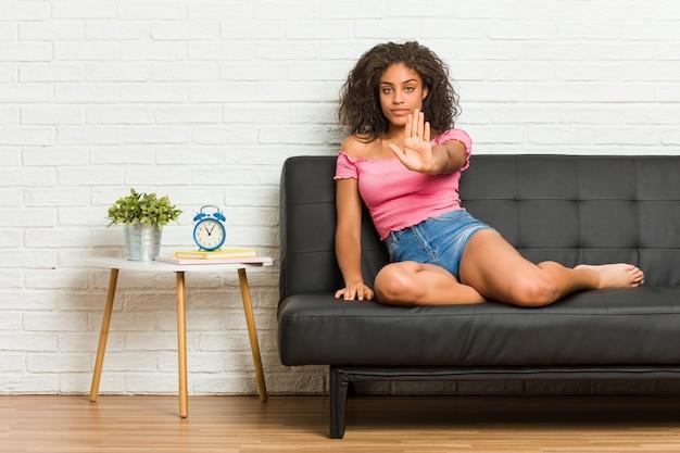 Jovem americana africano sentado no sofá em pé com a mão estendida, mostrando o sinal de stop, impedindo-o.