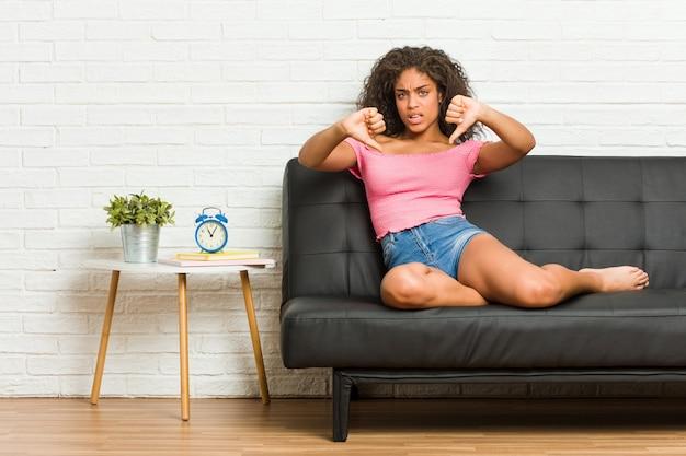 Jovem americana africano sentado no sofá mostrando o polegar para baixo e expressando antipatia.