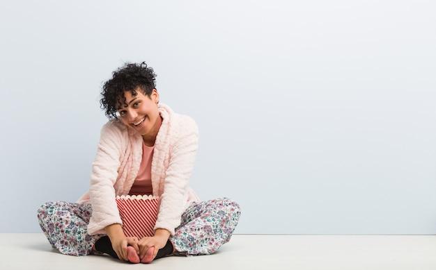 Jovem americana africano sentado segurando uma caixa de pipoca