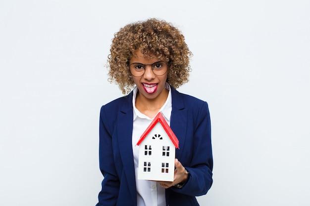 Jovem americana africano, sentindo nojo e irritado, enfiar a língua para fora, não gostar de algo desagradável e nojento com o modelo de casa