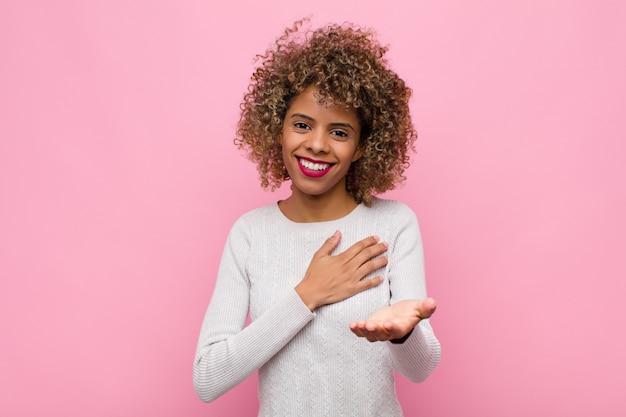 Jovem americana africano, sentindo-se feliz e apaixonado, sorrindo com uma mão ao lado do coração e a outra esticada na frente contra a parede rosa