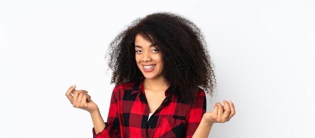 Jovem americana africano sobre parede fazendo dinheiro gesto