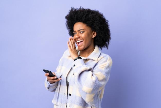 Jovem americana africano usando telefone celular na parede roxa sussurrando algo
