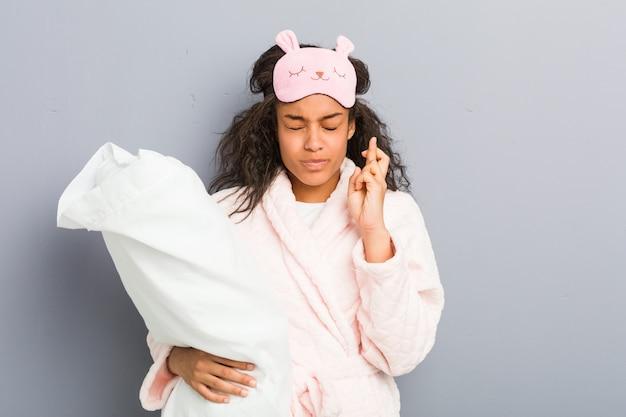 Jovem americana africano vestindo um pijama e uma máscara de dormir segurando um travesseiro cruzando os dedos por ter sorte