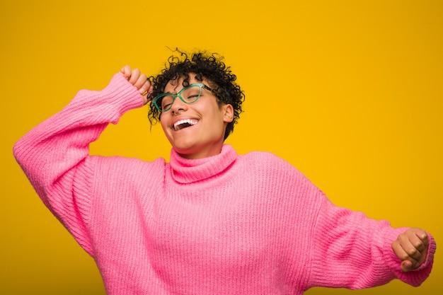 Jovem americana africano vestindo um suéter rosa dançando e se divertindo.