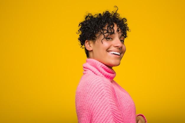Jovem americana africano vestindo um suéter rosa parece de lado sorridente, alegre e agradável.