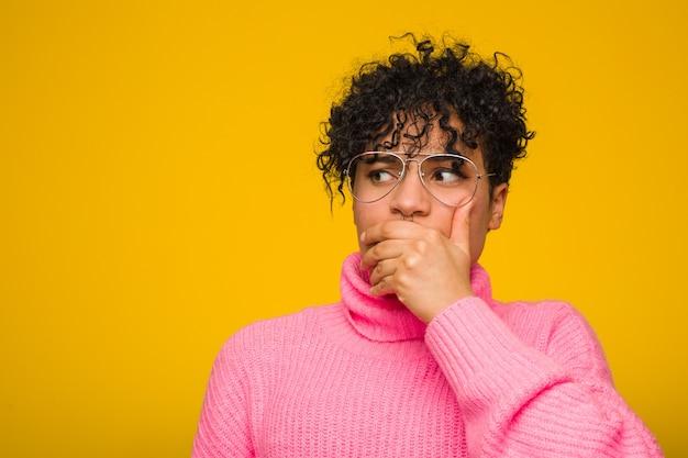 Jovem americana africano vestindo um suéter rosa pensativo para uma boca coberta com a mão.