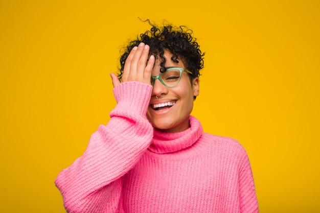 Jovem americana africano vestindo um suéter rosa se divertindo cobrindo metade do rosto com palm.