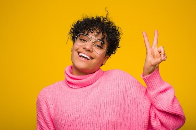 Jovem americana africano vestindo uma blusa rosa alegre e despreocupada, mostrando um símbolo de paz com os dedos.