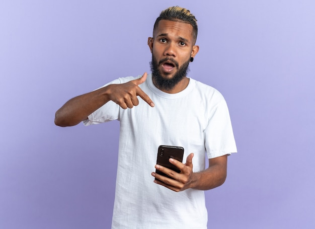 Jovem americano africano com camiseta branca segurando um smartphone apontando