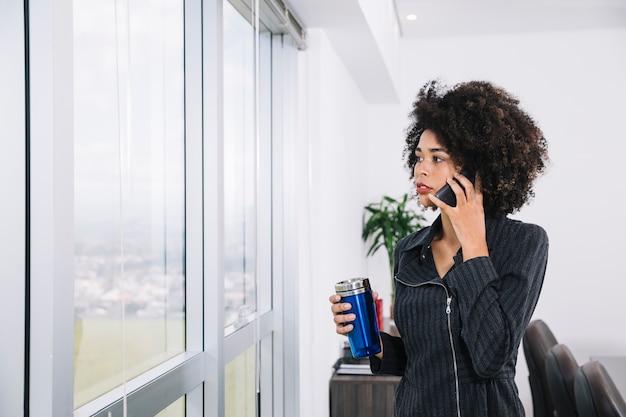 Jovem americano africano com garrafa térmica falando no smartphone perto da janela