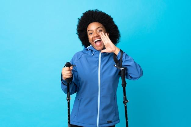 Jovem americano africano com mochila e pólos de trekking isolados no azul gritando com a boca aberta