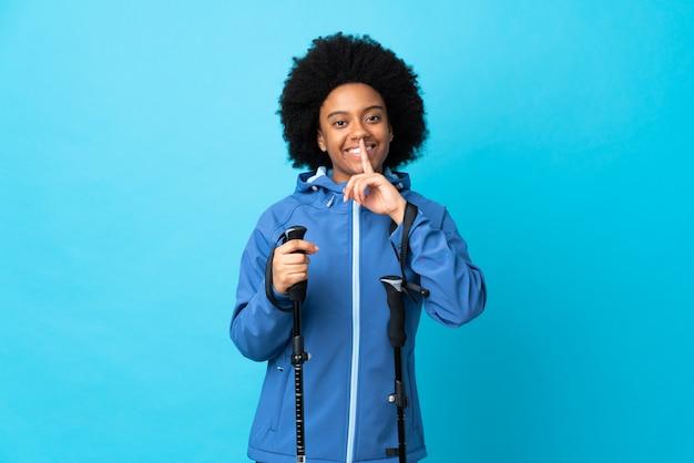 Jovem americano africano com mochila e pólos de trekking isolados no azul, mostrando um sinal de gesto de silêncio colocando o dedo na boca