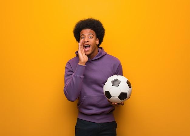 Jovem americano africano esporte homem segurando uma bola de futebol gritando algo feliz para a frente
