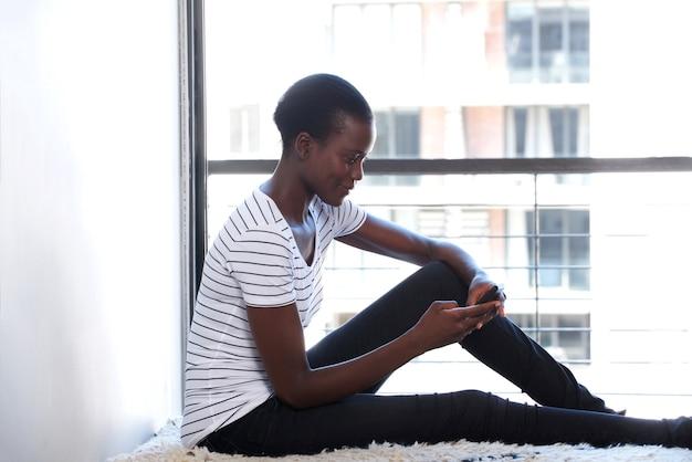 Jovem, americano africano, femininas, usando, telefone móvel, por, janela, casa