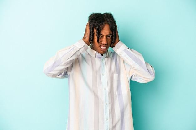 Jovem americano africano isolado em um fundo azul, cobrindo as orelhas com as mãos.