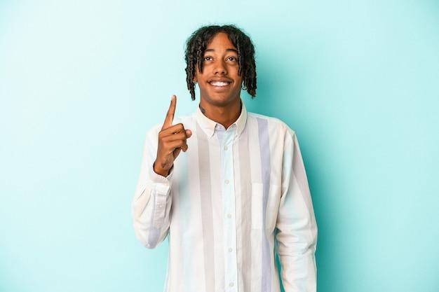 Jovem americano africano isolado em um fundo azul indica com os dois dedos anteriores mostrando um espaço em branco.