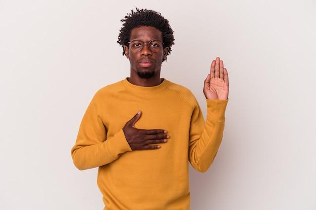 Jovem americano africano isolado no fundo branco, fazendo um juramento, colocando a mão no peito.
