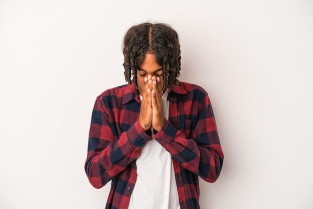 Jovem americano africano isolado no fundo branco orando, mostrando devoção, pessoa religiosa em busca de inspiração divina.
