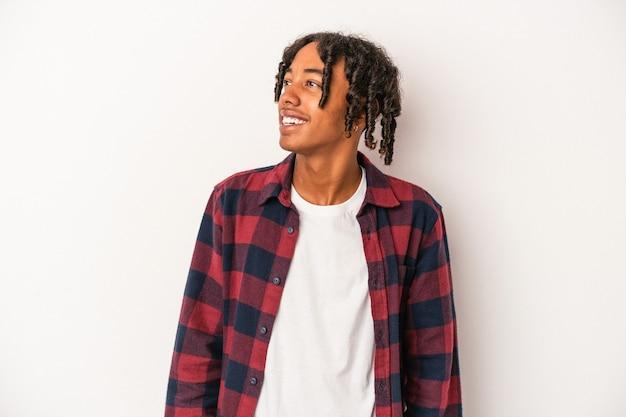 Jovem americano africano isolado no fundo branco relaxado e feliz rindo, pescoço esticado, mostrando os dentes.