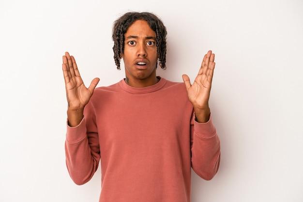 Jovem americano africano isolado no fundo branco surpreso e chocado.