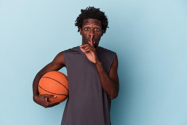 Jovem americano africano jogando basquete isolado em um fundo azul, mantendo um segredo ou pedindo silêncio.
