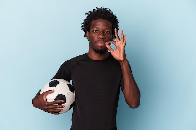 Jovem americano africano jogando futebol isolado em um fundo azul com os dedos nos lábios, mantendo um segredo.