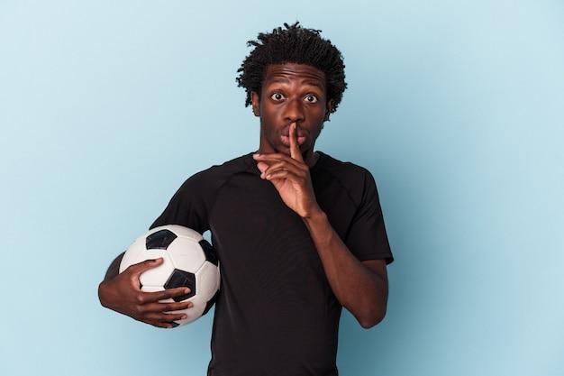 Jovem americano africano jogando futebol isolado em um fundo azul, mantendo um segredo ou pedindo silêncio.