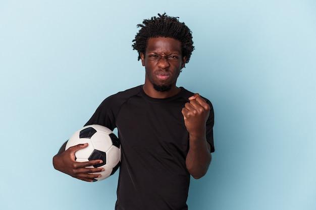 Jovem americano africano jogando futebol isolado em um fundo azul, mostrando o punho para a câmera, expressão facial agressiva.