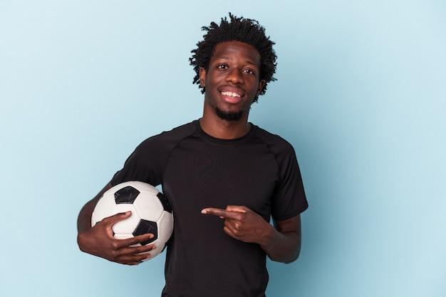 Jovem americano africano jogando futebol isolado em um fundo azul, sorrindo e apontando de lado, mostrando algo no espaço em branco.