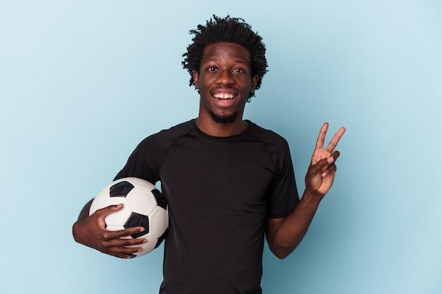 Jovem americano africano jogando futebol isolado no fundo azul, alegre e despreocupado, mostrando um símbolo de paz com os dedos.