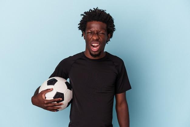 Jovem americano africano jogando futebol isolado no fundo azul, gritando muito zangado e agressivo.