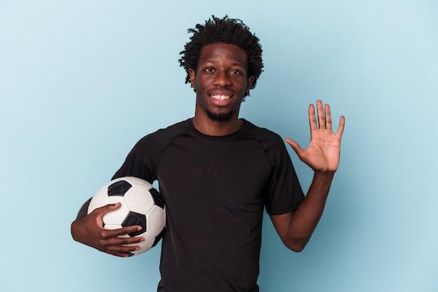 Jovem americano africano jogando futebol isolado no fundo azul, sorrindo alegre mostrando o número cinco com os dedos.