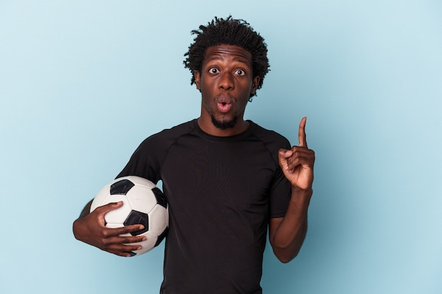 Jovem americano africano jogando futebol isolado no fundo azul, tendo uma ótima ideia, o conceito de criatividade.