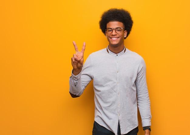 Jovem americano africano mostrando o número dois