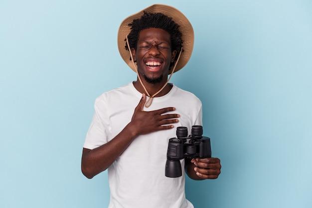 Jovem americano africano segurando binóculos isolados no fundo azul ri alto, mantendo a mão no peito.