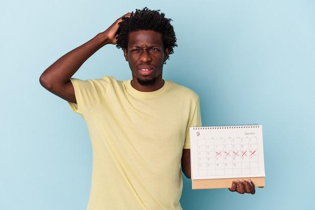 Jovem americano africano segurando o calendário isolado em um fundo azul, sendo chocado, ela se lembrou de uma reunião importante.