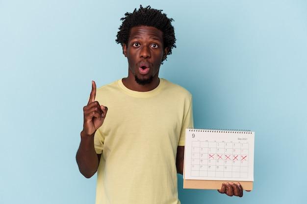Jovem americano africano segurando o calendário isolado no fundo azul, tendo uma ótima ideia, o conceito de criatividade.