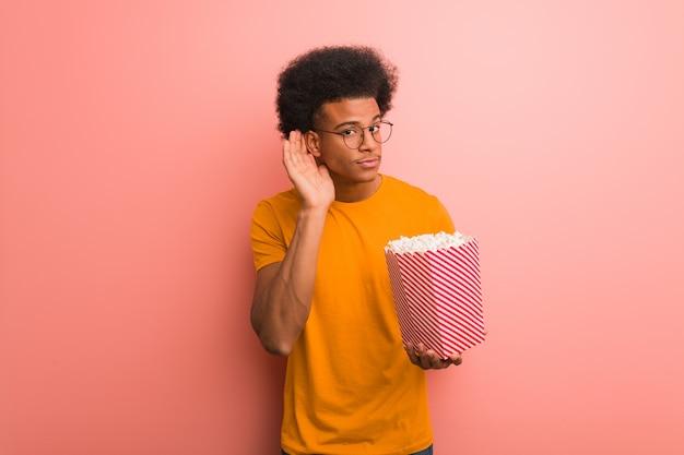 Jovem, americano africano, segurando, um, balde pipoca, tente, escutar, um, bisbolhetice