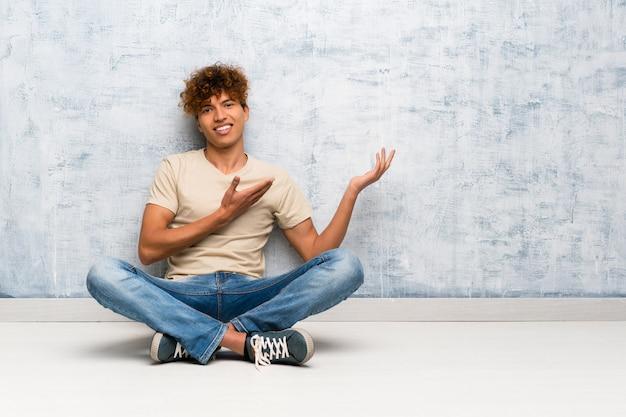 Jovem americano africano sentado no chão, estendendo as mãos para o lado por convidar para vir