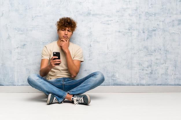 Jovem americano africano sentado no chão pensando e enviando uma mensagem