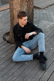 Jovem americano bonito sexy em jeans elegantes, descansando perto de uma árvore no terraço de verão na cidade