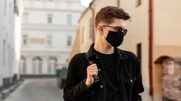 Jovem americano com penteado em óculos de sol da moda na elegante jaqueta jeans preta com elegante máscara preta médica caminha na rua em dia ensolarado.