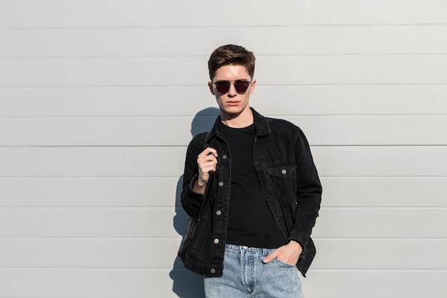 Jovem americano moderno com óculos de sol da moda e roupas jeans casuais elegantes