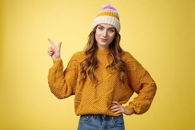 Jovem amiga confiante e bonita dizendo para você comprar o produto, apontando imensamente o canto superior esquerdo, sorrindo, segurar a mão na cintura, autoconfiante, funcionário ajudar o cliente a escolher o melhor produto, fundo amarelo