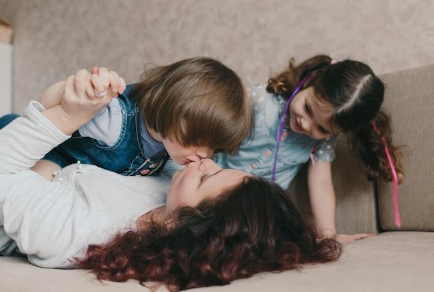 Jovem amorosa mãe e filha se beijam enquanto brincavam deitados no sofá. o conceito de felicidade familiar