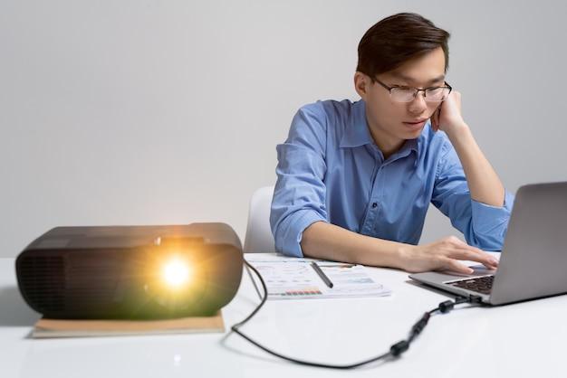 Jovem analista asiático pensativo em óculos, sentado à mesa com o projetor e usando o laptop enquanto trabalha na apresentação