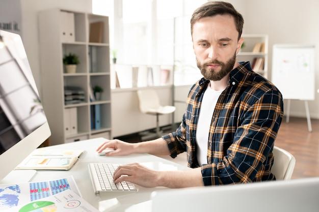 Jovem analista casual sério sentado ao lado do computador, digitando e olhando para a tela do laptop por perto enquanto analisa os dados